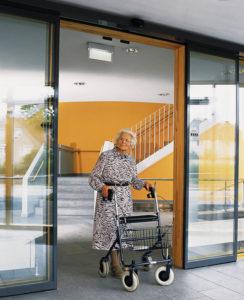 Frau im höheren Alter fährt mit Rollator durch Schiebetür