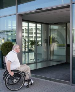 Mann im hohen Alter fährt mit Rollstuhl durch Geze Tür