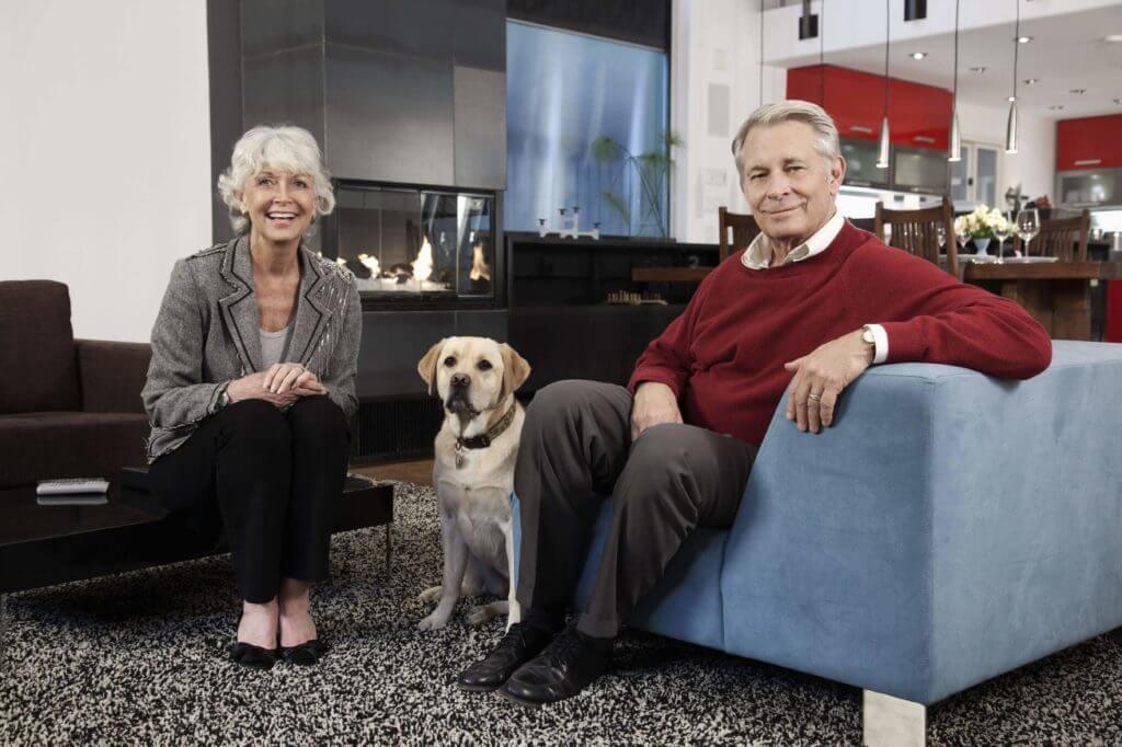 Barrierefreiheit: Ehepaar im hohen Alter sitzen mit ihrem Hund im Wohnzimmer