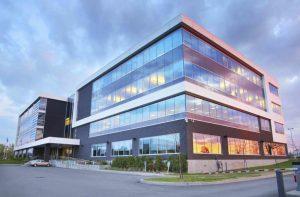 Unternehmensberatung: Gebäude aus Glas mit barrierefreier Rampe beim Eingang